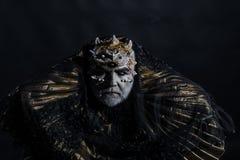 Re antico del mondo di fiaba che si siede sul trono, concetto di fantasia Vecchie spine barbute dell'uomo cieco sulla sua testa i immagine stock
