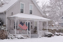 Re3d, Blue, and White. An American flag flies proudly on the porch of an 80 year old house as large snowflakes drift down on the snow-covered ground Royalty Free Stock Photo