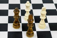 Re e regine di scacchi sulla scacchiera Fotografia Stock
