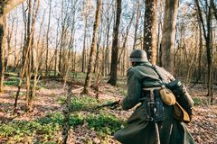 Re-enactor Dressed As German Infantry Wehrmacht Soldier Of The World War II. Hidden Walking With Weapon Rifle In Spring Forest stock photos