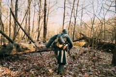 Re-enactor Dressed As German Infantry Wehrmacht Soldier Of The World War II. Walking With Weapon Rifle In Autumn Forest stock images