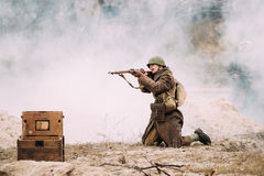 Re-enactor Dressed As Red Army Russian Soldier Of WWII Aiming With Rifle On Battlefield. Stock Photo