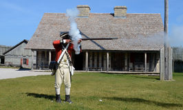 Re-enactor fires musket at Fort Michilimackinac Royalty Free Stock Photography