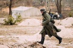 Re-enactor vestida como soldado In WW II de la infantería de Wehrmacht del alemán que corre en campo de batalla Celebración del 7 Fotografía de archivo