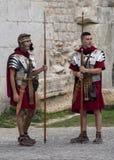 Re-Enactors kleedden zich aangezien Roman Legionnaires, om met Toeristen bij de poorten aan het Diocletian-Paleis wacht te stelle stock afbeeldingen
