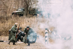 Re-enactors vestidos como soldados de Wehrmacht do alemão em Ww Ii estão correndo no campo de batalha Fotos de Stock Royalty Free