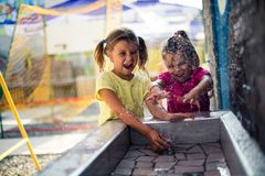 They`re having so much fun. Two little girls playing with water in playground. Close up stock photo