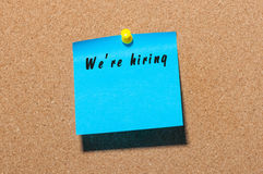 We're Hiring inscription on peace of paper pinned to notice board with empty space for text.  stock photos