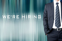 WE'RE HIRING sign on blur background with businessman Royalty Free Stock Photography