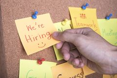 We re hiring text on sticky note or post is on cork bulletin. Billboard royalty free stock photos