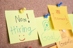 We re hiring text on sticky note or post is on cork bulletin. Billboard stock photo
