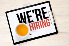 We`re hiring, text and tea cup. Over white wooden table royalty free stock photo