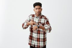 We`re late for meeting. Young good-looking tan-skinned unhappy guy with afro hairstyle in checkered stylish shirt Stock Photo
