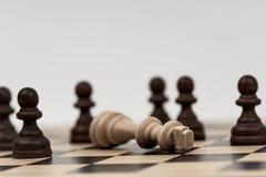 Re negli scacchi è caduto a parecchi pegni Immagine Stock