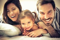 They`re one very happy family. Smiling family in bed. Space for copy stock photo