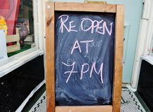 Re open at 7pm blackboard sign Stock Image