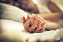 They`re the perfect match. Young couple in bed. Focus is on hands. Space for copy. Close up. Focus on hands stock photography