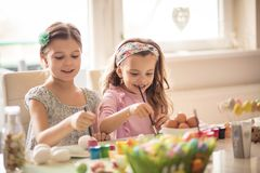 They`re into their arts and crafts. Little girls coloring Easter egg stock photo