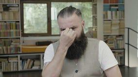 Reação sonolento de um homem de bocejo com a barba que toca em sua cara para manter-se acordado - filme