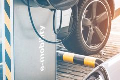 Reabastecimento do automóvel para a e-mobilidade no carro do fundo, roda dos carros bondes foto de stock