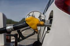 Reabastecimento no posto de gasolina Pistola amarela velha com uma mangueira no tanque de gás do carro Foto de Stock