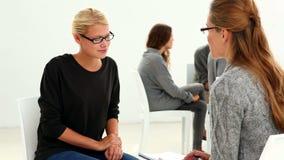 Reabilite o grupo que senta-se em um círculo com o terapeuta que fala à menina separadamente vídeos de arquivo