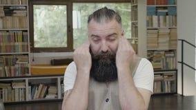 Reacción de un hombre joven cansado soñoliento que se sienta en el escritorio que bosteza y que intenta permanecer despierta - almacen de metraje de vídeo