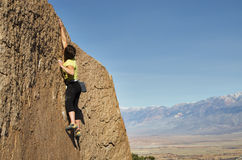 Reach. A woman rock climber makes a big reach for the top royalty free stock photo