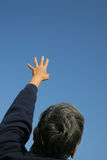 Reach. A man reaching out towards the sky Royalty Free Stock Images