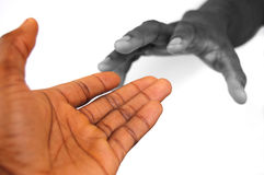 Reach of Care. This is an image of a pair of hands reaching out to each other. One in black and white, the other in colour Royalty Free Stock Photos