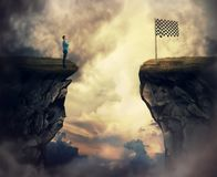 Reach the finish flag. Business problem as a young man stand on a cliff need to go the other side to reach the finish flag. Overcome problems, successful royalty free stock photos