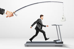 Reach a goal concept with businessman running on a treadmill for Royalty Free Stock Images