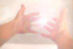 Reach for the light. Hands in soft focus reaching towards a light Stock Photo