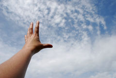 Reach sky. Reaching with hand toward the sky of clouds Stock Photo