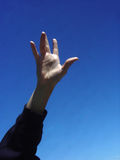 Reach for the Sky. A hand reaching upwards towards the sky stock image
