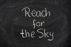 Reach for the sky phrase on blackboard Stock Photo
