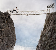 Reach the success with difficult. Achievement business goal and Difficult career concept. Businessman runs through a shaky bridge to get to the flag. Achievement stock photo