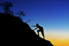 Reach for success. A hiker raising his arms in enjoyment against a sunset background on a mountain Royalty Free Stock Photography