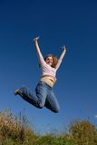 Reach to the Sky. Young female happily  jumping in field on a hill with the sky as background Stock Image
