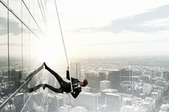 Reach the top. Concept of competition with businessman climbing office building with rope stock illustration