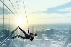 Reach the top. Concept of competition with businessman climbing office building with rope royalty free illustration