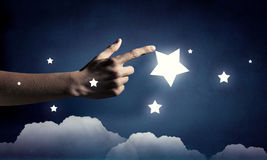 Reach and touch the star. Human hand touching with finger star in sky Royalty Free Stock Image
