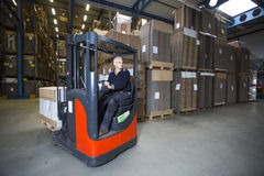 Reach truck. Driving around the corner in a warehouse where cartboard boxes are stored royalty free stock images