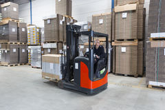 Reach Truck driving. Reach truck passing by in a warehouse where cartboard boxes are stored on palets stock photography