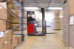 Reach truck. Forklift driving past an isle in a warehouse at speed. A panned image, with stock and cardboard boxes in the shelfs of the storage racks Royalty Free Stock Photo