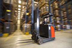 Reach Truck. Panning shot of a reach truck forklift driving by in a warehouse stock photos