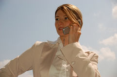 Always reachable 3. Attractive woman with mobile phone in front of blue sky Stock Photo
