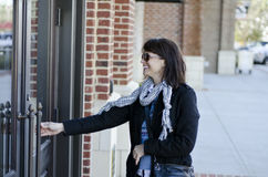 Reaching. Woman in glasses reaching to open a door to an office royalty free stock images