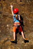 Reaching. Young girl rock climbing at mountain crag Stock Images