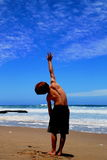 Reaching. Young boy standing on beach reaching out to the sky Royalty Free Stock Photos